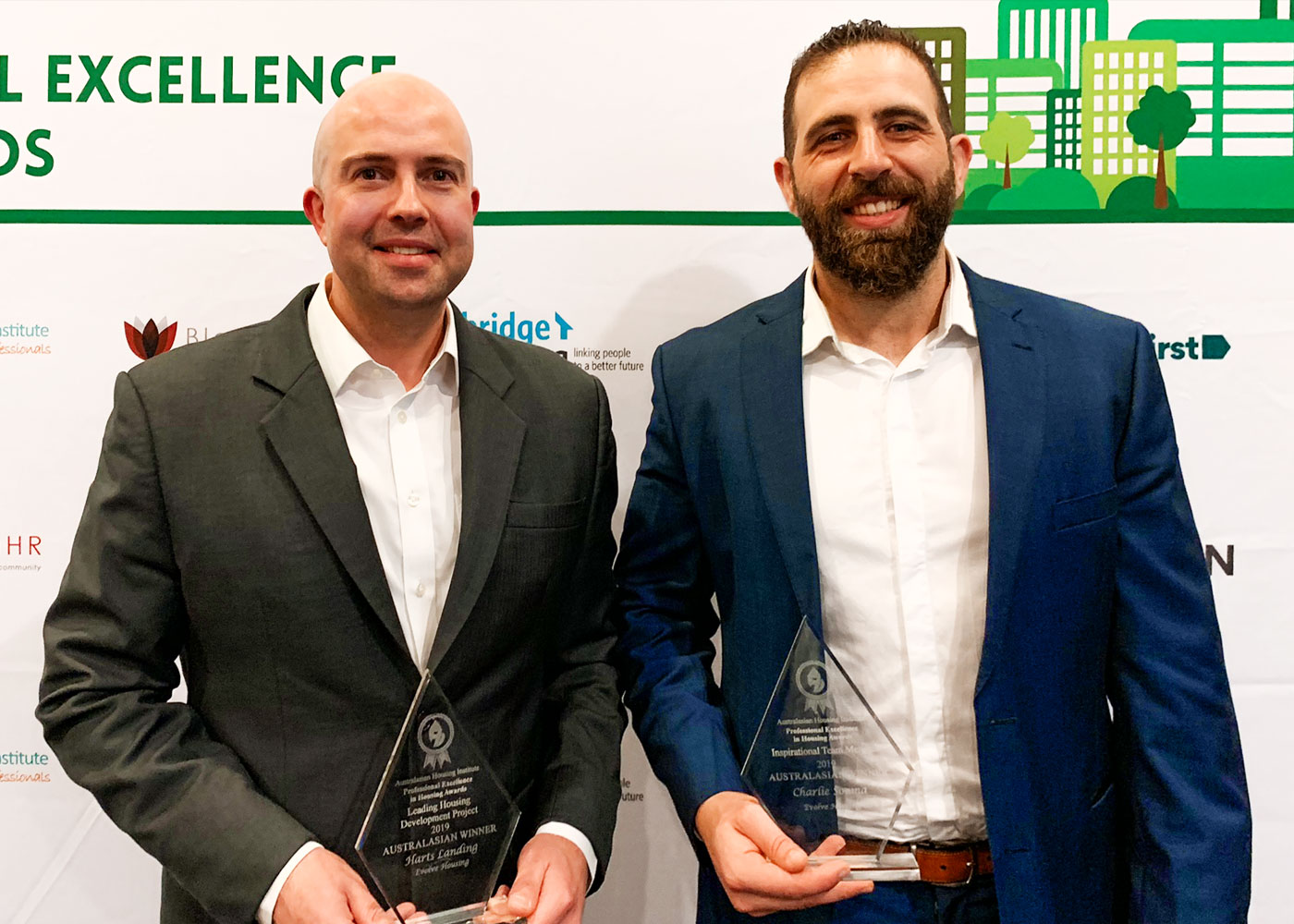Two men smile to camera while holding awards