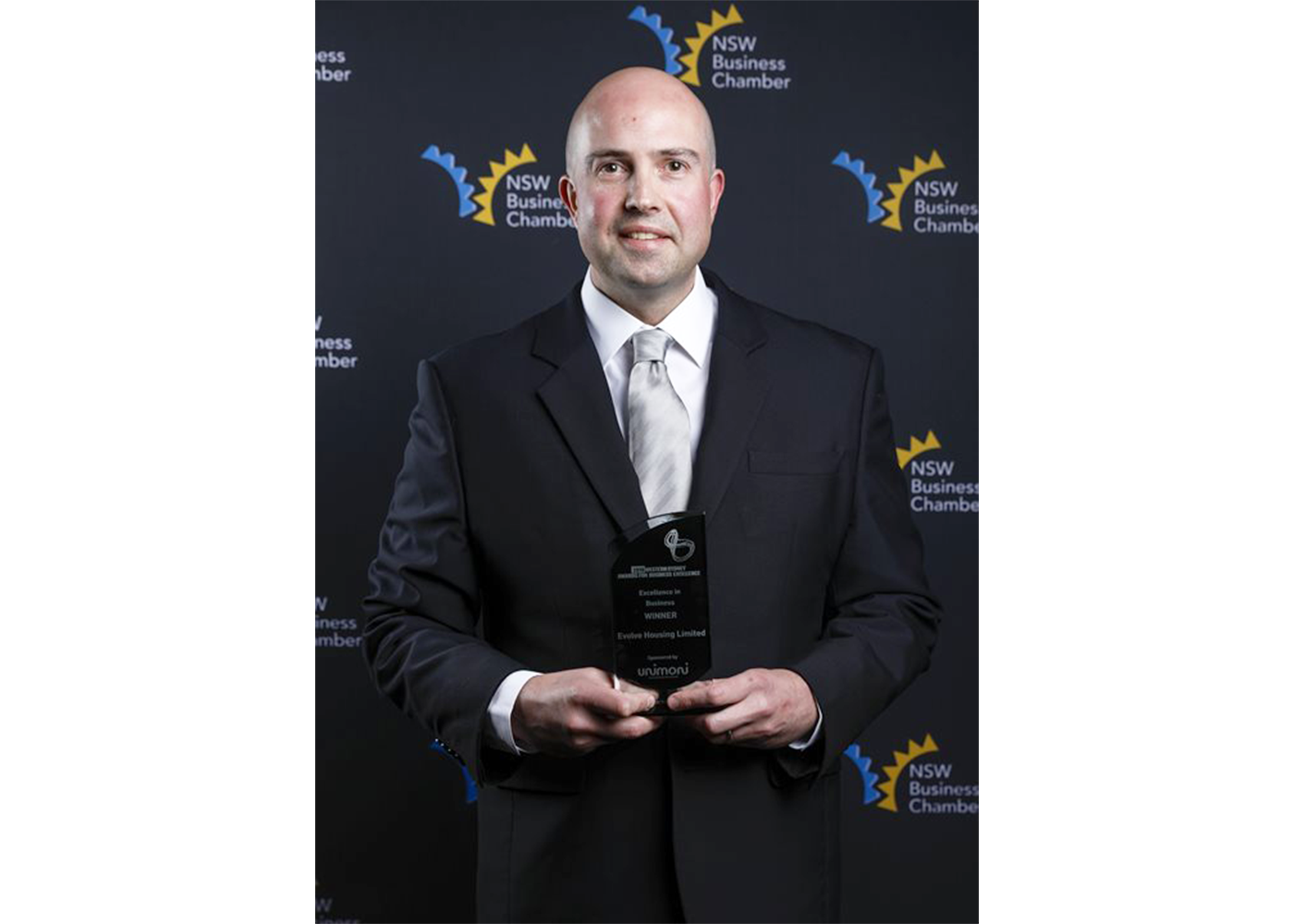 Man holds award and smiles to camera